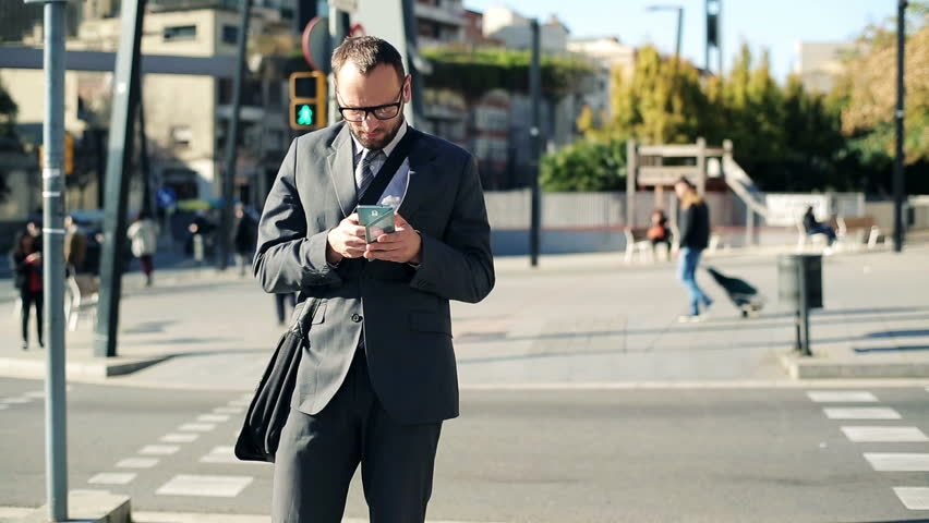 Young businessman with smartphone crossing city street