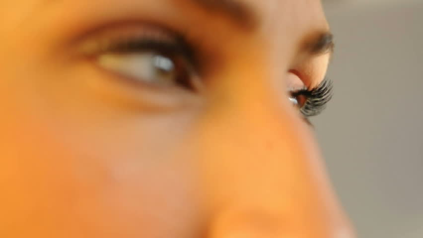 eyes of a young attractive woman with macro focus change, eyes only, short depth of field, blurred background - HD stock video clip