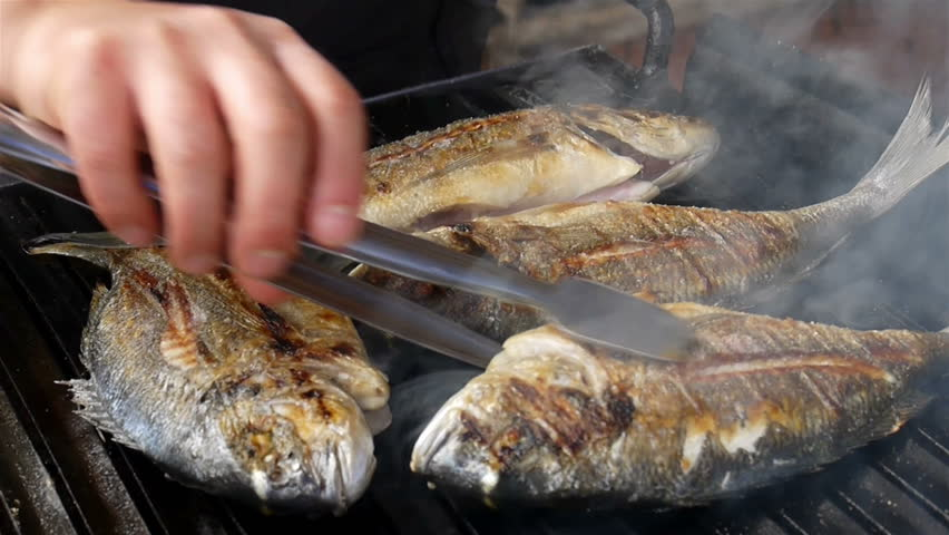 Dorado, Sea Bream, Gold mackerel, madai fish grilled over coals with rotating