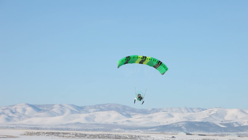 Powered parachute flying across a ice and snow covered lake in winter. Central Utah winter recreation and sport. Pilot in aircraft waves. Bright green colored parachute. - HD stock footage clip