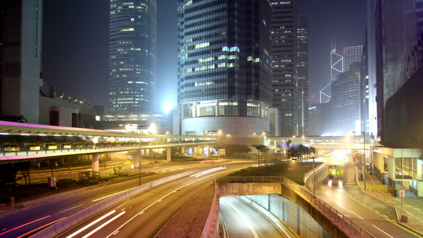 Cityscape timelapse at night. Hong Kong. Busy traffic across the main road at rush hour.