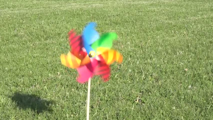 Rehilete turning with the Summer or Spring wind. Spinwheel in a lawn or turf of green grass. Colorful Reguilete toy waiting for children to play. Inexpensive outdoors or screen away time.