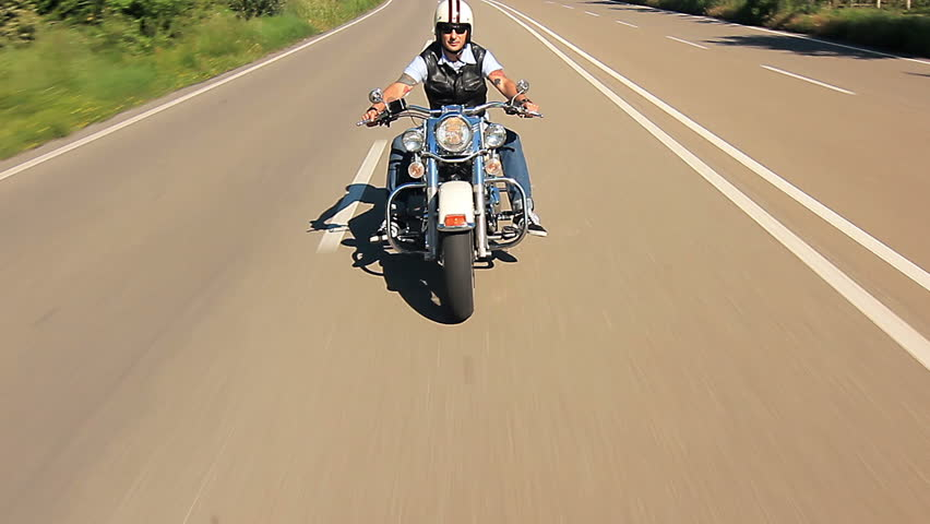 man riding his motorcycle n on a highway follow shot car point of view