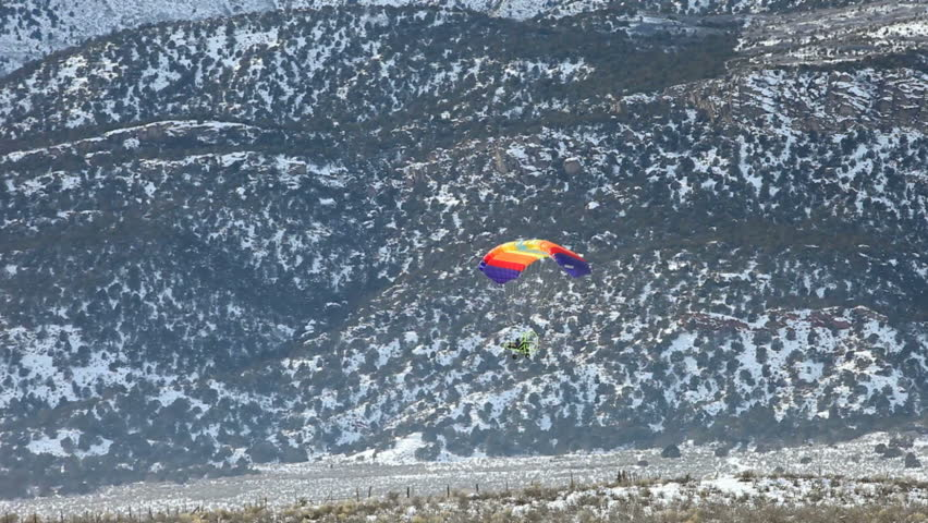 Powered parachute flying low along snow covered mountains in winter. Central Utah winter recreation and sport.  - HD stock video clip