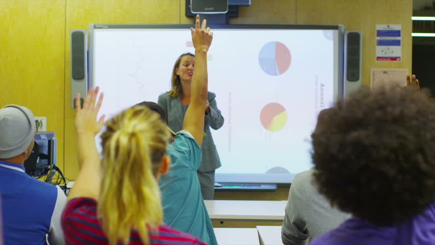 Teacher in class, explaining a subject to her students.
