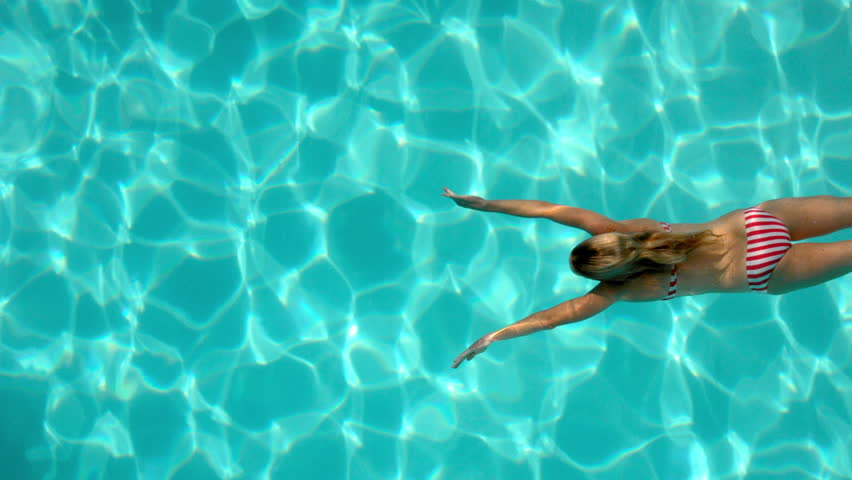 Woman swimming in the pool underwater overhead in slow motion - HD stock video clip