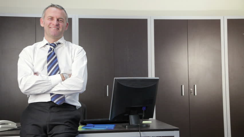 Multiple shots of mid adult businessman looking at camera in office (sequence)