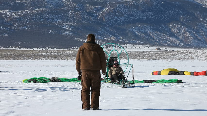 MORONI, UT- CIRCA JAN 2010: Wade Roundy of Moroni watches pilot prepare for flight circa Jan 2010 in Moroni, Utah, USA. Powered parachute start and take off on ice and snow covered lake in winter. - HD stock video clip