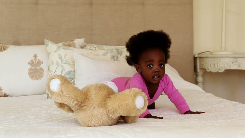 Cute baby girl playing with teddy bear on bed at home in bedroom