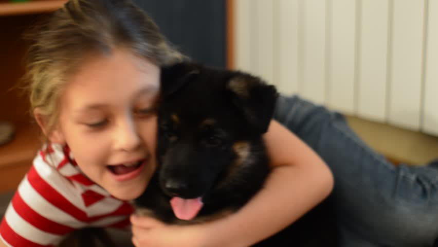 girl talking to a German Shepherd puppy
