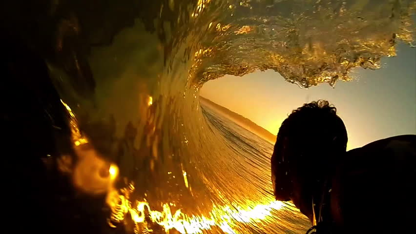 High contrast POV shot of silhouetted surfer as he rides through the barrel of a dark orange wave, with the sun setting ahead of him