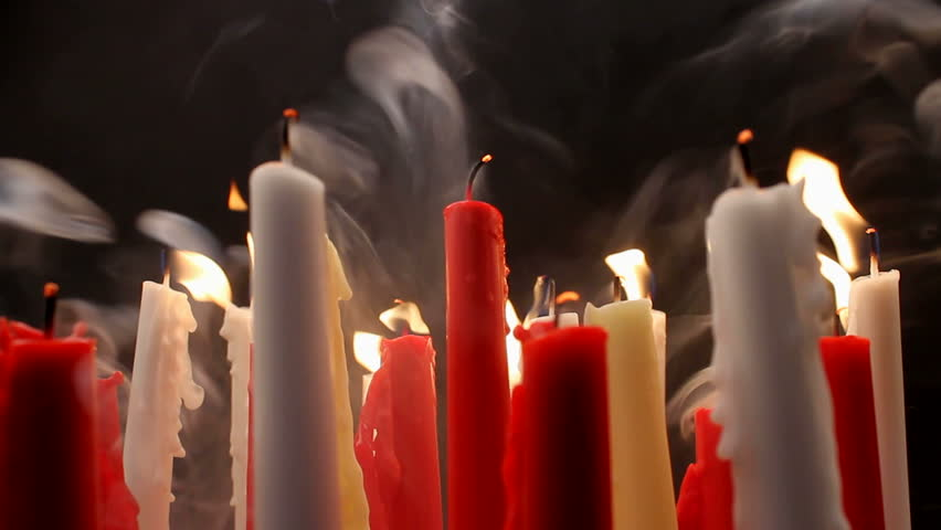 Burning candles in motion, blown out, create curls of thick smoke, hazy, black background, motorized slider. 1080p