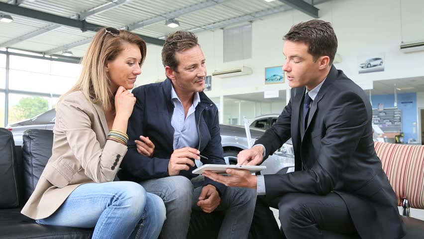 Couple with car dealer signing purchase contract on tablet