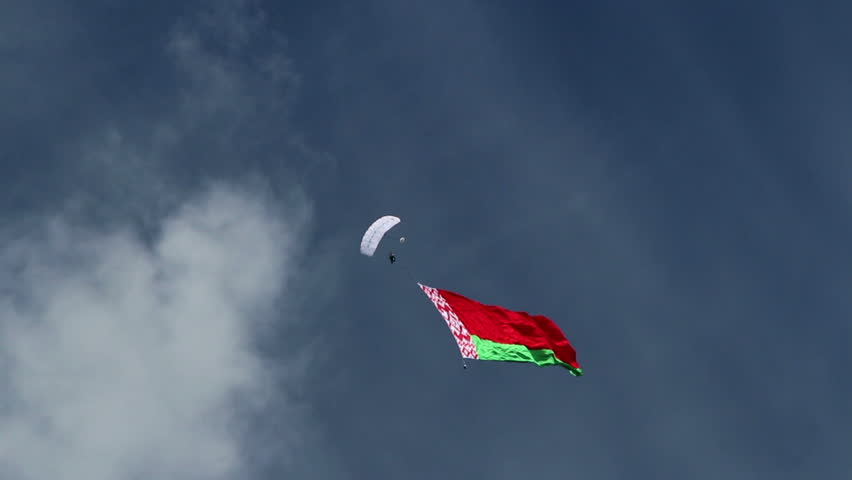 Airshow, Belarus, Minsk - 21.06.2014: Airshow, devoted to the 80th anniversary of DOSAAF. paratrooper carries a national flag of Belarus