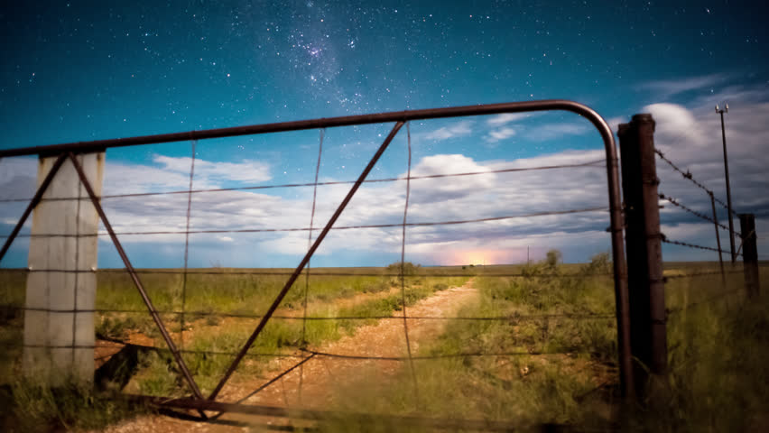 Linear timelapse at night time with a dramatic moonlit landscape scene in the Karoo, through a rusted farm gate with scattered clouds.