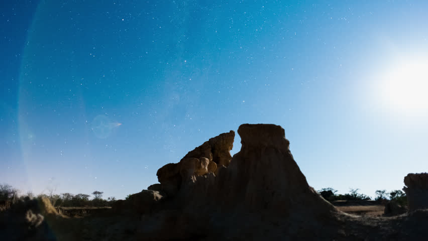 Linear, push-in night timelapse of abstract landscape with silhouette eroded rocks while the moon is setting and the Milky Way moves into the frame.