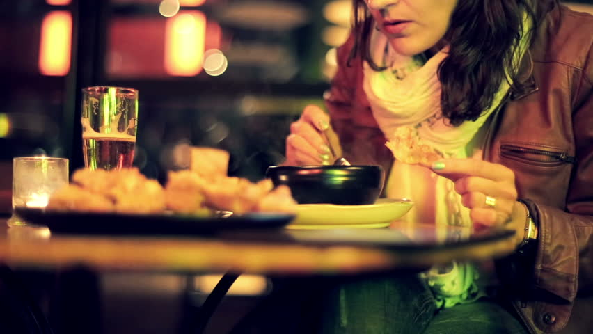 Woman eating soup late at night in restaurant