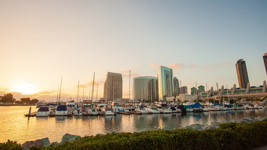 Sunset over San Diego Downtown. Timelapse in motion ( hyperlapse ). Shot from Embarcadero Marina Park South. View on skyscapers and yachts. Transition from day to night. Zoom in.