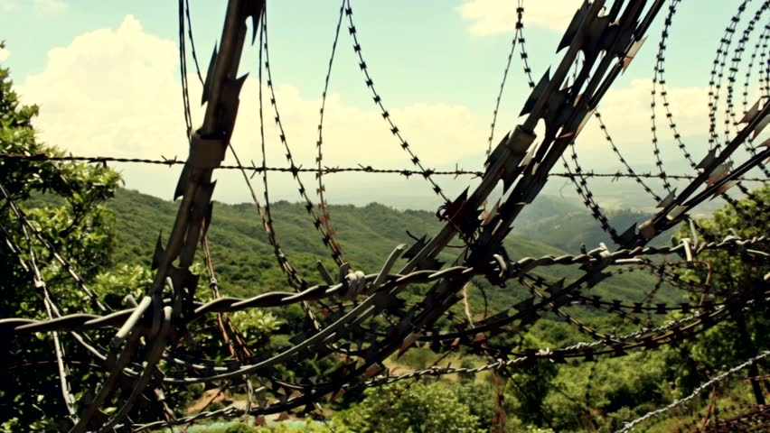 Barbed wire blocking beautiful nature. Focus changes from foreground to background.