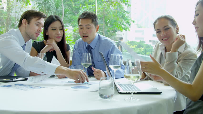 Caucasian Asian Chinese group financial investors collaborating future business plans using spreadsheets lunch meeting close up shot on RED EPIC