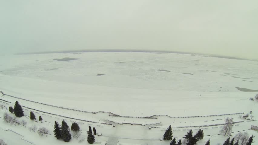 Quay with monument and snowbound shore of frozen river at winter day during snowfall. Aerial view - HD stock footage clip