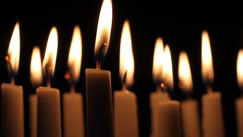 group of dimly lit burning white candles create mood