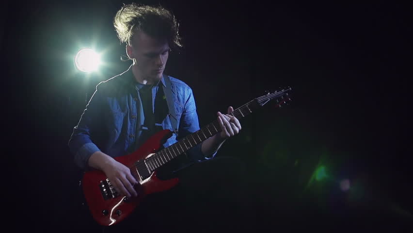 Slow motion of super cool guitarist getting down to his own music in the dark