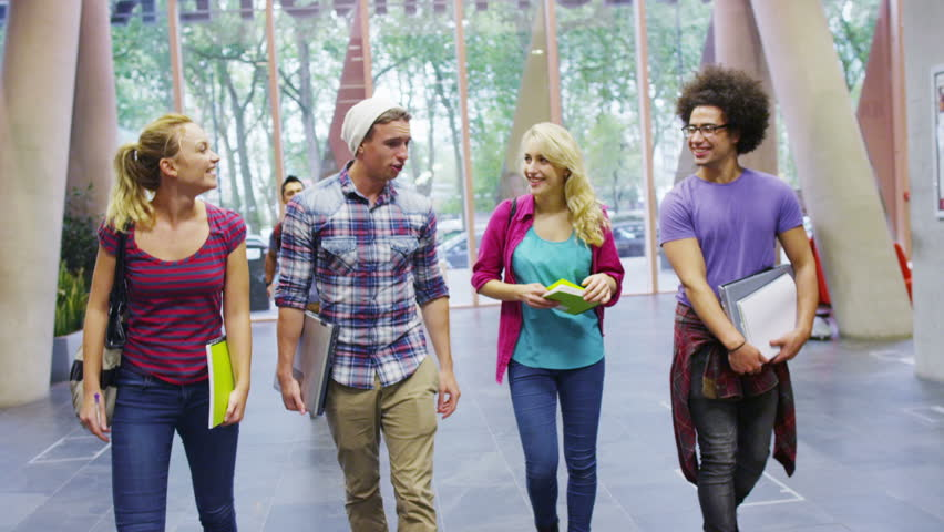 Diverse group of student friends walking together through modern university