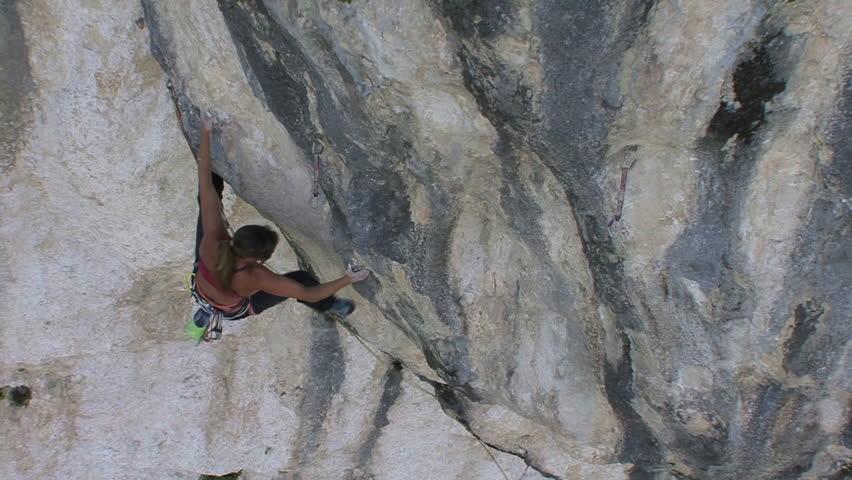 FRANCE 2011 - Woman climber on rock face, high angle long shot, adjusting holds - HD stock footage clip