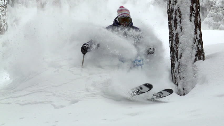Slow motion skier carving through thick fresh powder snow, multiple shots,