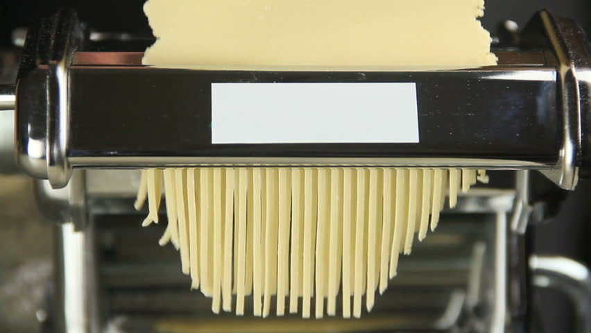 Close up of fresh spaghetti pasta coming out of pasta machine making a pile of fresh spaghetti on bench.