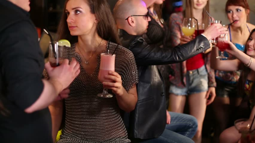 Eight men and women relax with cocktails at party in bar of night club