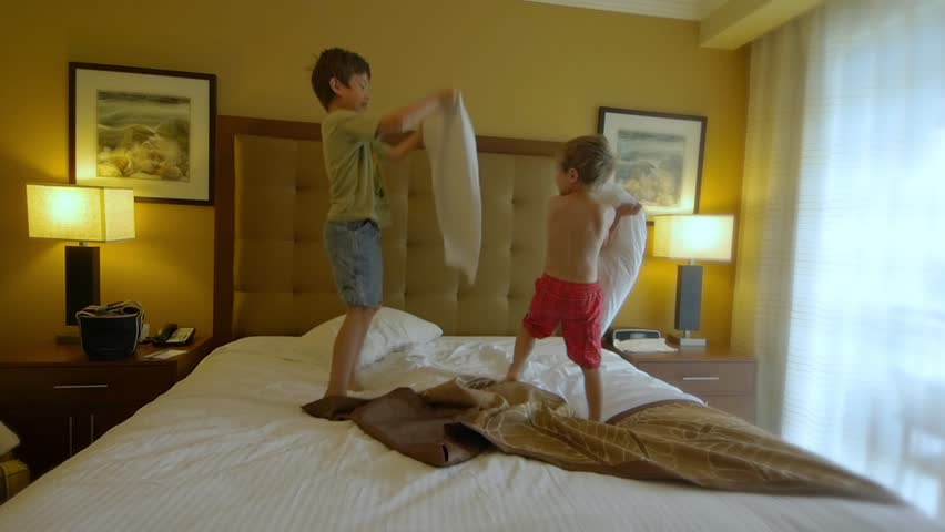 Two boys having a pillow fight on a king size bed. slow motion video clip - HD stock footage clip