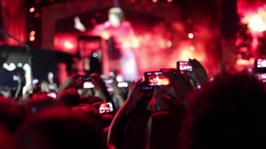 Euphoric crowd making a video and photo with smartphone and tablet.