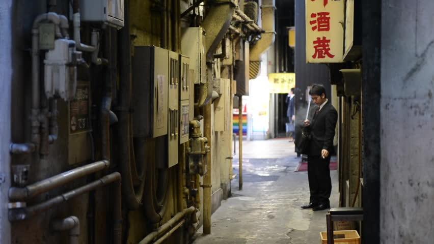 Japanese salary-man smoking in an alley near Yurakucho, Tokyo