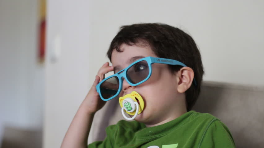 Kid with pacifier watching 3D content on TV | Shutterstock HD Video #6848746
