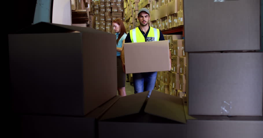 Delivery driver loading his van with boxes in a large warehouse - 4K stock video clip