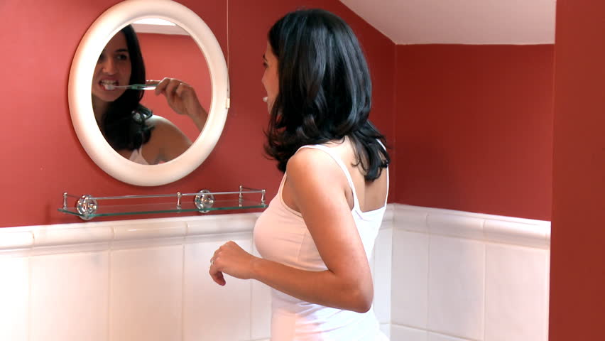 Brunette woman brushing her teeth in the bathroom  - HD stock video clip