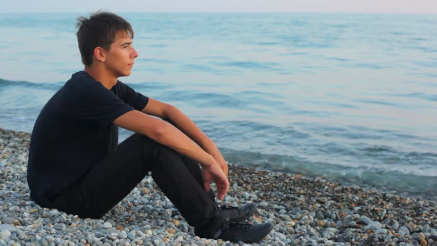 teenager sits on pebble beach and looks at sea, profile  - HD stock video clip