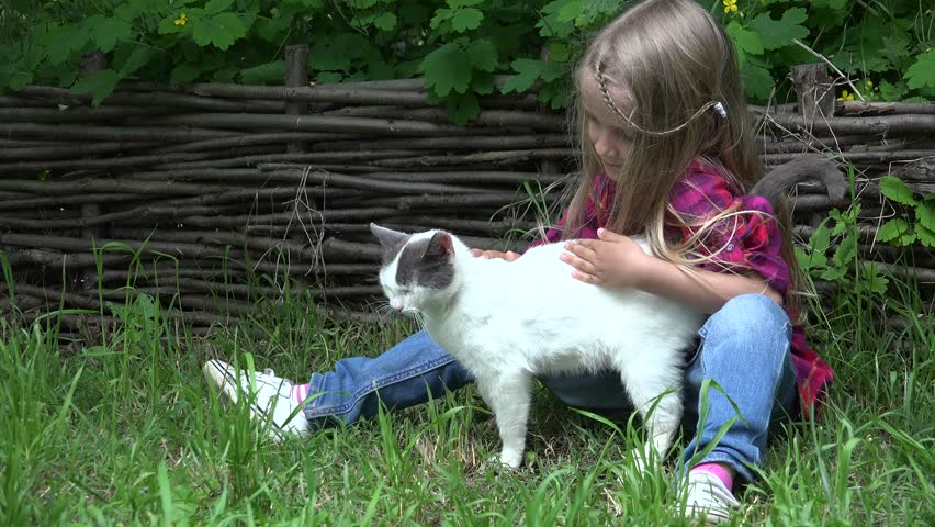 Ultra HD 4K View of a Happy Caucasian Little Girl Petting her Cat on Green Grass in Yard at Countryside, Blonde, Smiling Child Playing with a Kitten, Children and Pets - 4K stock video clip