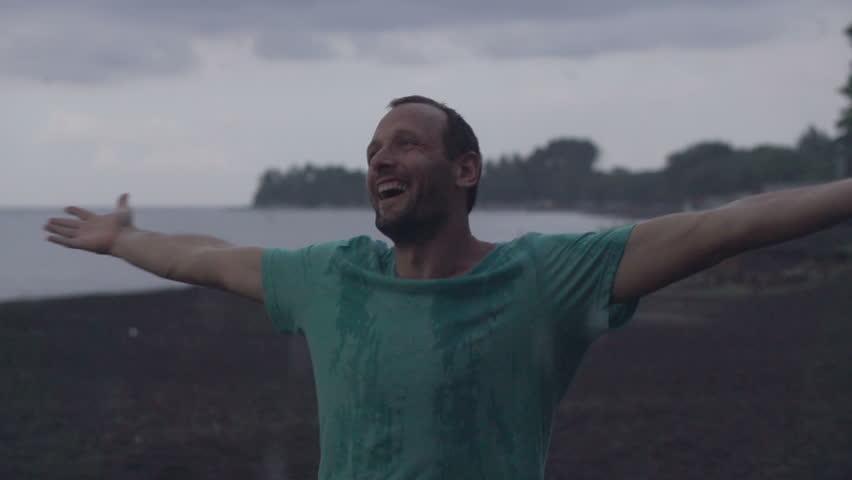 Happy man enjoying rain on the beach, super slow motion, 240fps