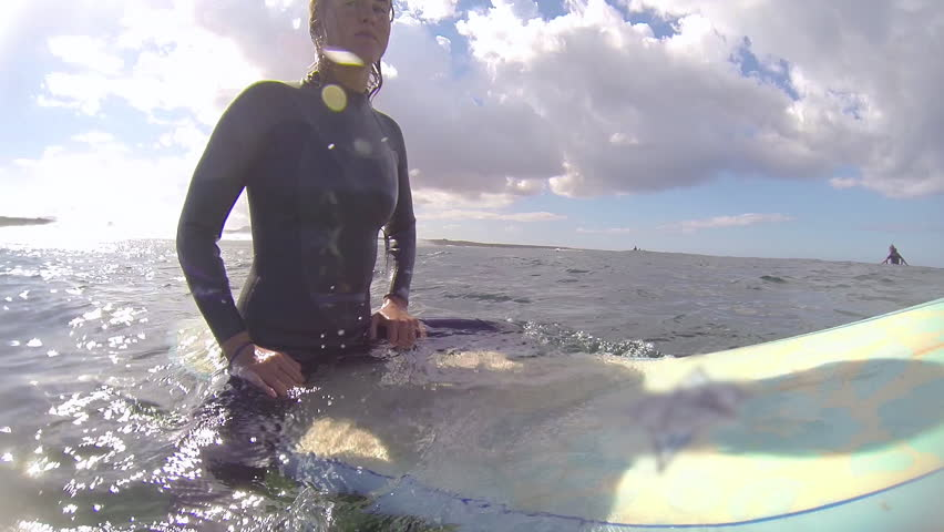 UNDERWATER: Female surfer sitting on a surfboard - HD stock footage clip