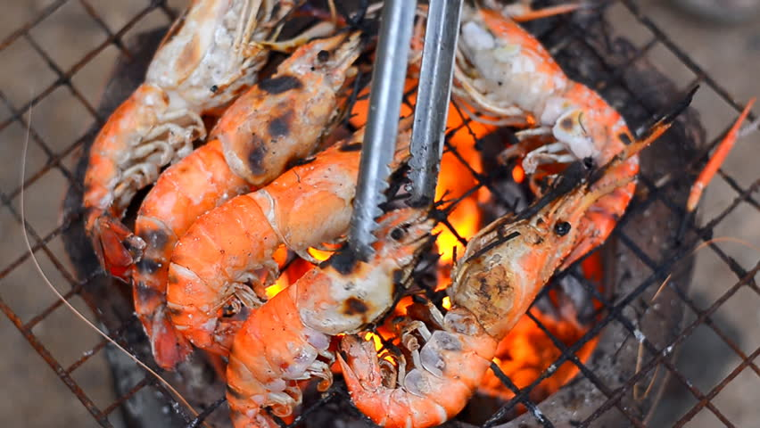 delicious shrimp on grill with flames in background