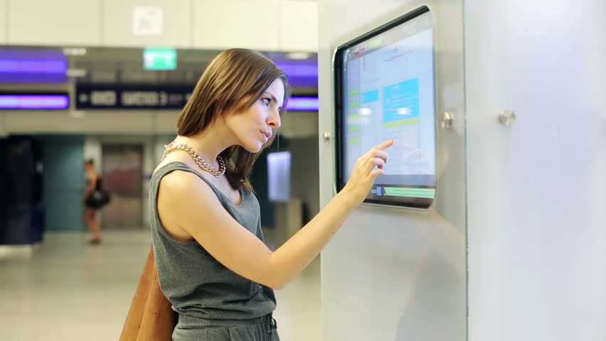 Woman checking trains timetable at modern touchscreen info kiosk