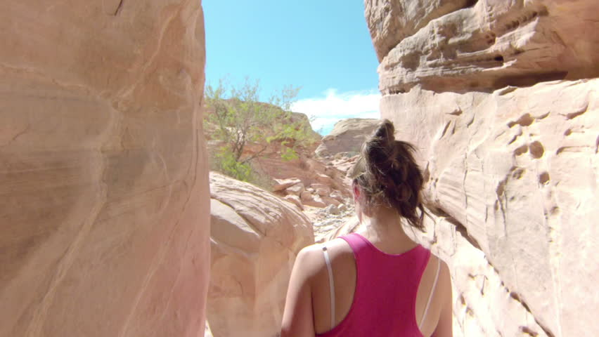 Following a woman hiking through a narrow canyon. As it opens up, she walks out into the rocky desert of Valley of Fire National Park.