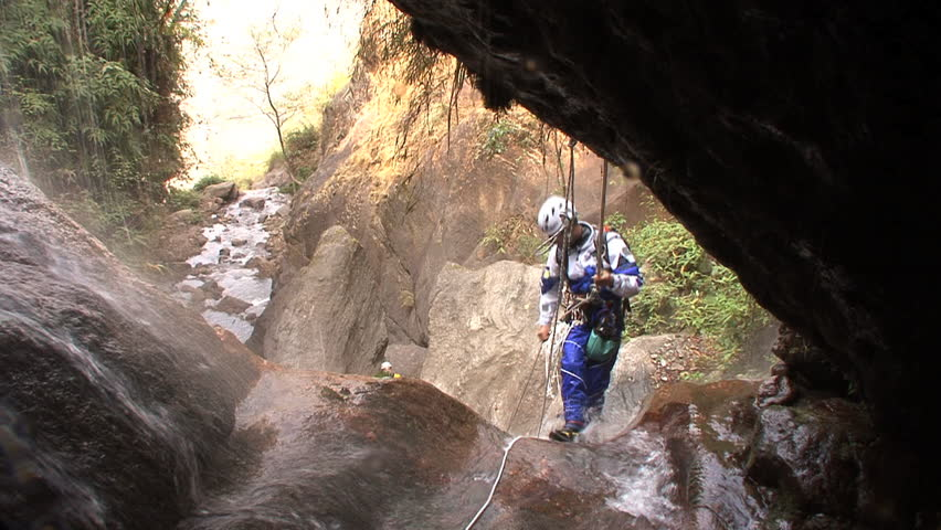 A canyoneer canyoning down a narrow gorge, stream visible in background - HD stock video clip