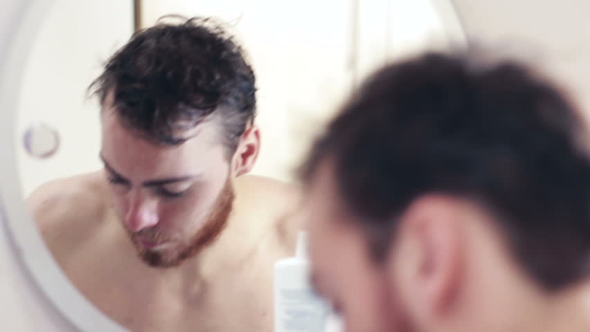 Young man uses moisturizer in bathroom after having a shower, shallow depth of field