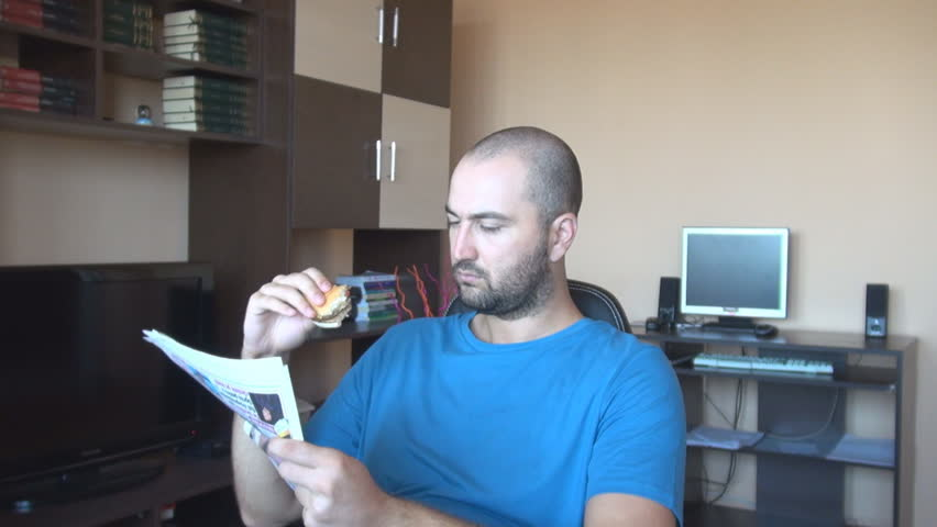 Young man eating hamburger home, reading newspaper in the morning, unhealthy food for lunch meal - HD stock video clip