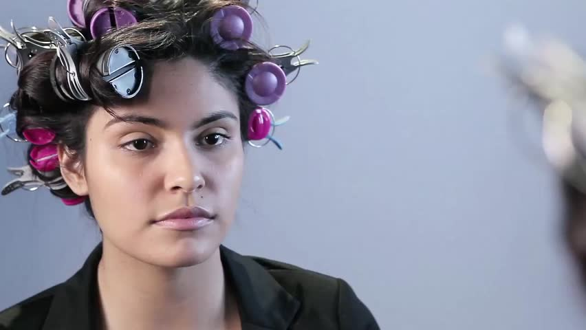 A latina woman with curlers in her hair looks into the for Adda beauty salon cartierul latin