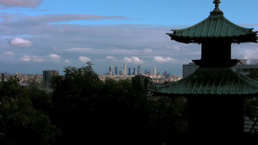 Downtown Los Angeles in the Distance: Medium tight shot silhouetting shrubbery and a pagoda which go on further to frame a distant view of the Los Angeles skyline.   Shutterstock HD Video #699937